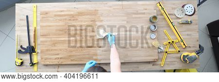 A Joiner Polishes A Wooden Surface. Carpenter Tools Lie On The Table