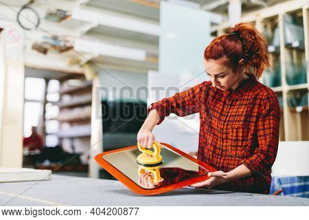 Glazier woman worker holding a glass pane with suction cups in workshop. Industry and manufactory production