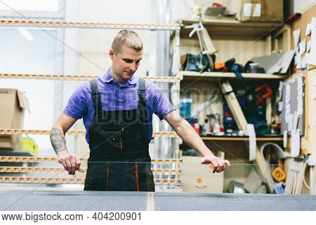 Glazier worker preparing mirror glass in workshop. Industry and manufactory production