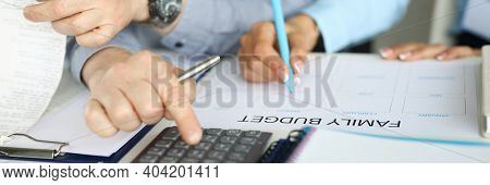 A Couple In Business Clothes Makes A Family Budget On Paper. Reliable And Functional Personal Financ