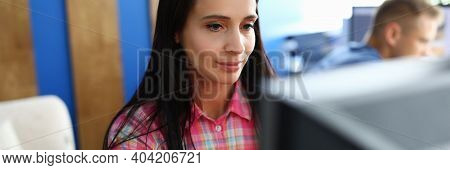 A Young Woman Sits In An Office At The Monitor And Works Intently. Employees Sit In The Same Room