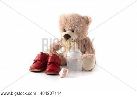 Teddy Bear, Pacifier,feeding Bottle And Shoes Isolated On White Background