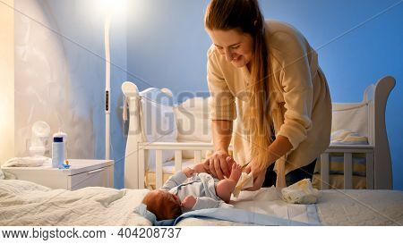 Young Smiling Mother Undressing Her Crying Baby At Night To Change Messy Diapers. Baby Hygiene