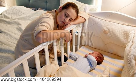Young Tired And Exhausted Mother Fallen Asleep While Rocking Crib Of Her Newborn Baby At Night. Conc