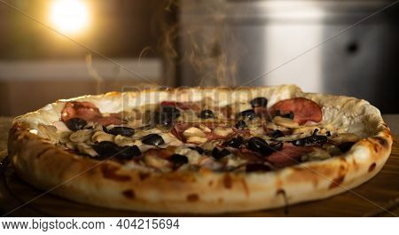 There Is A Large Round Hot Pizza On The Table, And Steam Above It. Pizzeria Menu.