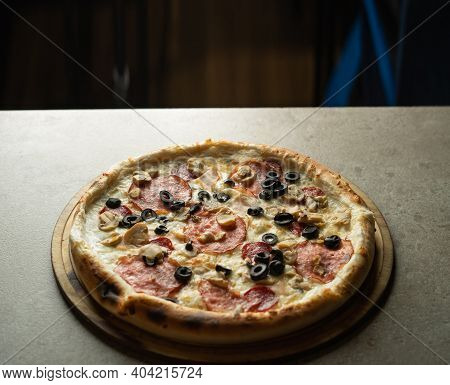 Hot Pizza With Olives, Cheese And Sausage On A Wooden Board On A Gray Background. Ready-made Pastrie