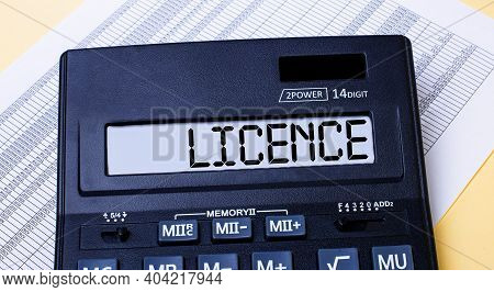 A Calculator Labeled Licence Is On The Table Near The Report. Financial Concept
