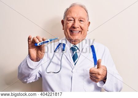 Senior grey-haired doctor man wearing stethoscope controlling temperature using thermometer smiling happy and positive, thumb up doing excellent and approval sign