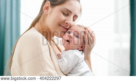Closeup Portrait Of Happy Smiling Mother Holding And Looking On Her Newborn Baby Boy. Concept Of Fam