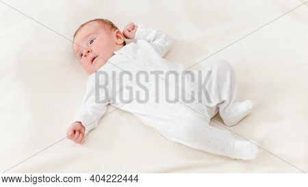 View From Above On Adorable 1 Months Old Baby Boy Lying On White Blanket On Bright Sunny Day.