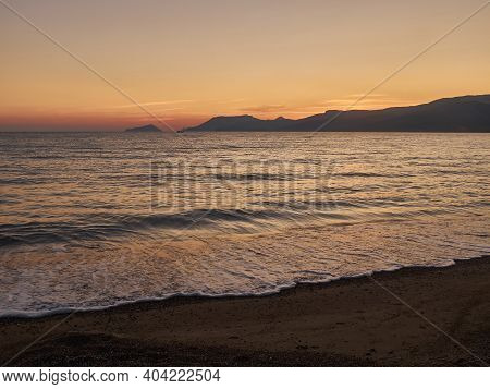 Sunset Landscape With Sea And Mountains At The Horizon. Sea Coast In The Dusk. Evening Surf On Sandy