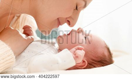 Closeup Shot Of Beautiful Young Mother Cuddling And Stroking Her Little Baby Son Lying On Bed In Sun