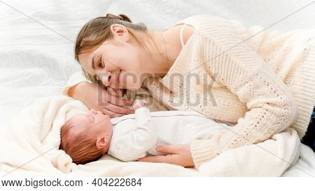 Top View Of Beautiful Smiling Mother Lying Next To Her Newborn Baby And Looking On Son. Concept Of F