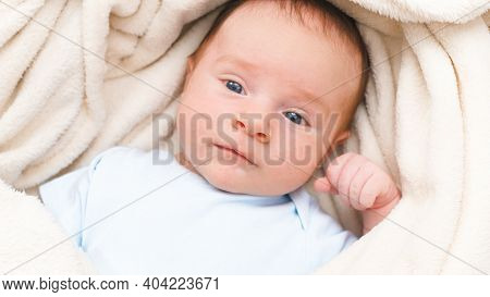 Top View Portrait Of 1 Months Old Little Baby With Blue Eyes Lying On White Soft Blanket On Bed And
