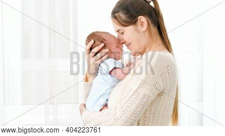 Portrait Of Happy Smiling Mother Cuddling And Looking On Her Newborn Baby Son Against Big Window At