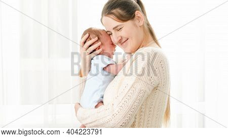 Portrait Of Beautiful Smiling Mother Holding And Stroking Her Newborn Baby Son At Big Window Against