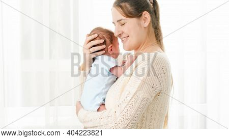Portrait Of Happy Smiling Mother Hugging And Holding Her Little 1 Months Old Baby Son Against Big Wi