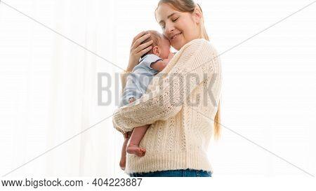 Portrait Of Mother Cuddling Newborn Baby In Sun Light Shining Through Big Window At House