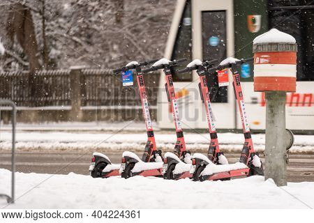 Augsburg, Bavaria, Germany - January 17, 2021: Voi Electric Rental Scooters Stand On The Side Of The