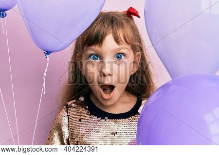 Little caucasian girl kid holding balloons afraid and shocked with surprise and amazed expression, fear and excited face.