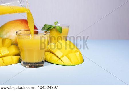 Mango Shake On Blue Background. Healthy Drinking Vitamin Smoothie. Fresh Tropical Mango Fruit Juice.