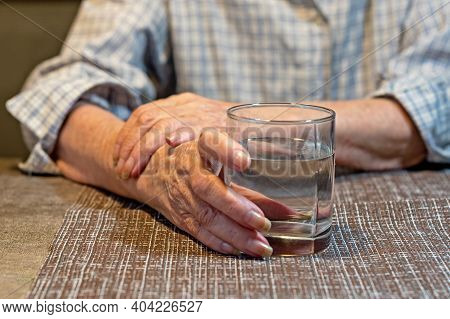 Elderly Woman Holds A Glass Of Water In Her Hands