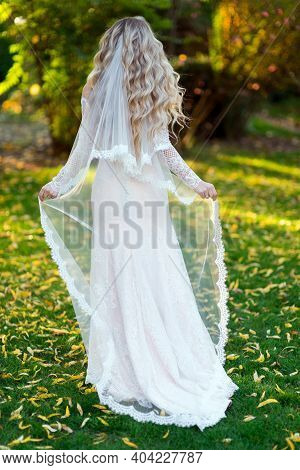 The Blonde Bride In A Wedding Dress Straightened The Veil With Her Back
