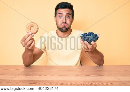 Young hispanic man eating breakfast holding donut and blueberries puffing cheeks with funny face. mouth inflated with air, catching air.
