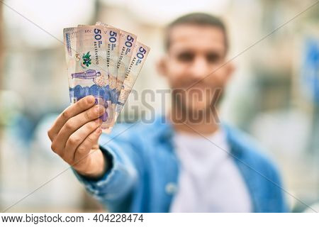 Young caucasian man smiling happy holding colombian pesos at the city.