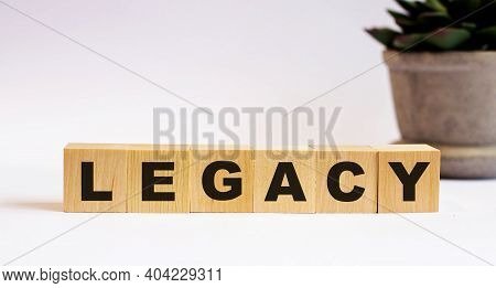The Word Legacy On Wooden Cubes On A Light Background Near A Flower In A Pot. Defocus