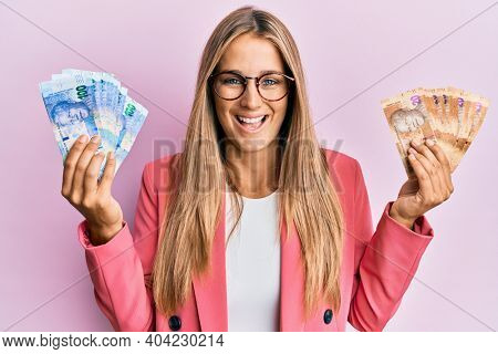 Young blonde woman wearing business style holding south african rands banknotes smiling and laughing hard out loud because funny crazy joke.