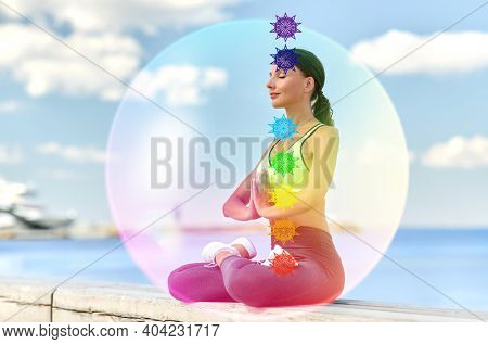 fitness, yoga and mindfulness concept - young woman meditating in lotus pose at seaside with seven chakra symbols