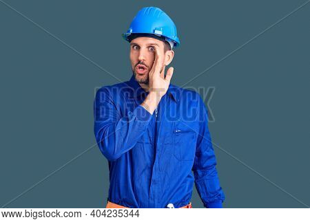 Young handsome man wearing worker uniform and hardhat hand on mouth telling secret rumor, whispering malicious talk conversation