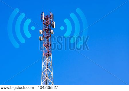 Cellular Base Station With Transmitter Antennas On A Telecommunication Tower On Against A Blue Sky.
