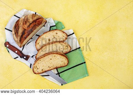 Freshly Baked Wheat Bread And A Cut Slice Of Bread On A Yellow Textured Background With Copy Space.