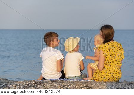 Young Mother With Three Children Is Resting On The Seaside. Back View. Family Holidays At The Seasid
