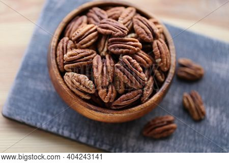 Pecan Nut Close-up In A Round Wooden Cup On A Black Shabby Board On Wooden Table Background.nuts And