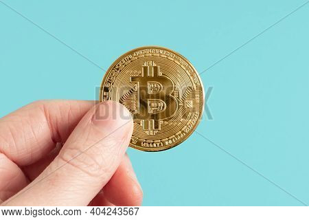 Gold Bitcoin Held Up Against A Bright Blue Background. Hand Holding Cryptocurrency