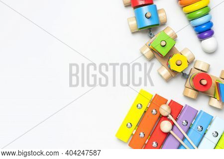 Children's Toys Made Of Natural Wood On White Background. Multi-colored Pyramid, Train, Xylophone In