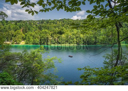 Lake And Paddleboat Framed By Tree Branches And Green Forest Illuminated By Sunlight In Plitvice Lak