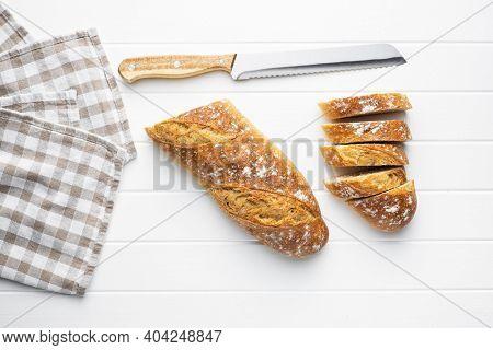 Crispy fresh baguettes. Sliced baguette on white table. Top view.