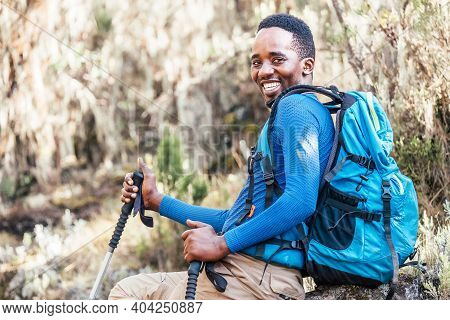 Portrait Of A Cheerfully Smiling African-american Ethnicity Young Man Sitting With A Backpack And Tr