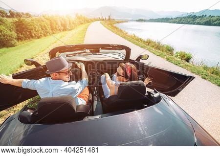 Couple In Love Getting Into The Convertible Auto Cabriolet And Starting A Trip. Couple Honeymoon, Tr