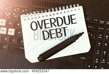White Paper Sheet With Text Overdue Debt On The Black Laptop