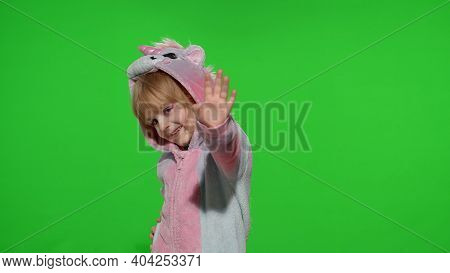 Little Smiling Blonde Child Girl 5-6 Years Old In Unicorn Costume Posing Waving Greeting With Hand I