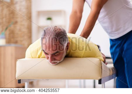 Old male patient visiting young male doctor chiropractor