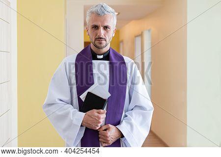 Catholic Priest Holding Envelope With Money During Pastoral Visit Called Kolenda In Poland