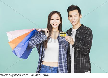 Happy Young Couple Shopping And Holding Shopping Bags And Man Showing Credit Card