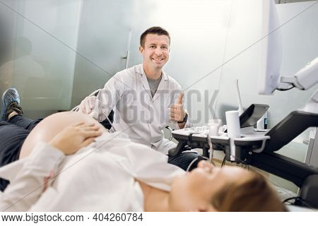 Professional Male Doctor Screening Of Pregnant Woman By Ultrasound, Smiling And Showing Thumb Up. Yo