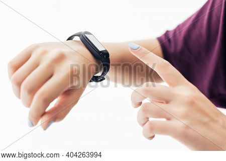 Girl with fitness tracker on her wrist pointing at the screen